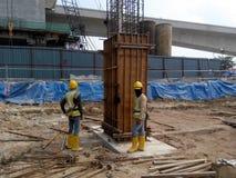 制造木材专栏模板的建筑工人在建造场所 免版税库存图片
