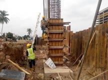 制造木材专栏模板的建筑工人在建造场所 库存照片