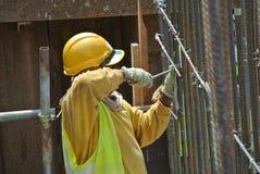 制造桩帽钢增强酒吧的建筑工人 免版税图库摄影