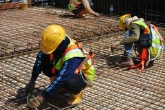 制造水泥板增强酒吧的建筑工人 免版税库存图片
