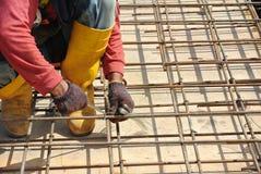 制造水泥板增强酒吧的建筑工人 免版税库存照片