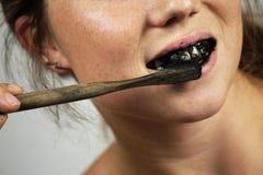 刷她的有一个黑牙膏的少妇牙与活跃木炭和黑色牙刷在白色背景牙的 免版税图库摄影