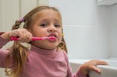 刷她的有一把牙刷的女孩孩子牙在卫生间里 图库摄影