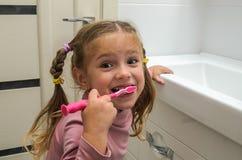 刷她的有一把牙刷的女孩孩子牙在卫生间里 免版税库存图片
