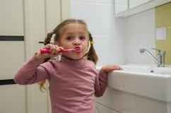 刷她的有一把牙刷的女孩孩子牙在卫生间里 库存图片