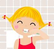 刷她的牙的一个小女孩 免版税库存图片