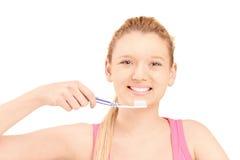 刷她的牙的一名美丽的白肤金发的妇女 免版税库存照片
