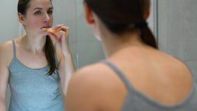 刷她的牙的俏丽的妇女在一个卫生间里早晨 早晨卫生学 股票视频