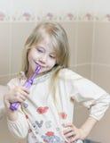 刷她的牙的女孩在有垂头丧气的眼睛的卫生间里 图库摄影