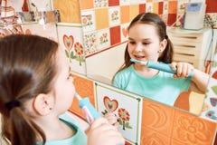 刷她的牙的小女孩在卫生间里 免版税库存图片