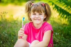 刷她的牙的愉快的小女孩 牙齿卫生学概念 免版税库存图片