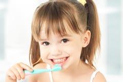刷她的牙的愉快的小女孩 免版税库存照片