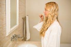 刷她的牙的白肤金发的妇女 库存图片