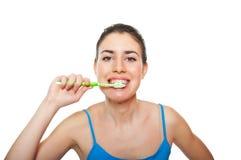 刷她的牙的逗人喜爱和愉快的妇女 图库摄影