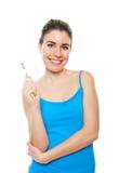 刷她的牙的逗人喜爱和愉快的妇女 免版税库存图片