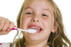 刷她的牙的逗人喜爱的女孩。 免版税库存图片