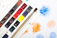 刷子、油漆和图画在纸在蓝色背景 库存图片