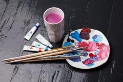 刷子、调色板和丙烯酸酯的颜色在地板上 免版税库存照片