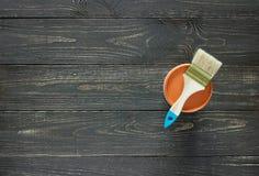 刷子和油漆罐头在黑暗的木背景 免版税图库摄影