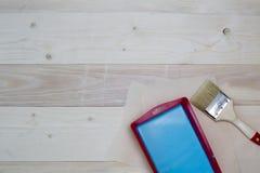 刷子和蓝色油漆在一个容器在木板 免版税库存图片
