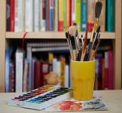 刷子和水彩照片在玻璃的在被弄脏的bookshe的 免版税库存图片