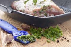 刷子用大蒜,荷兰芹和菜油卤汁在切板的 免版税库存照片