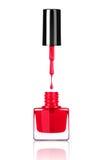 从刷子的指甲油水滴到在白色的瓶里 免版税库存图片