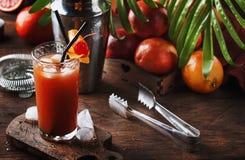 刷新低酒精鸡尾酒用伏特加酒、橙汁过去、血淋淋的桔子和冰块的夏天 木的表 选择聚焦 图库摄影