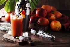 刷新低酒精鸡尾酒用伏特加酒、橙汁过去、血淋淋的桔子和冰块的夏天 木的表 选择聚焦 库存图片