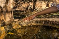 刷新在喷泉的ChildÂ的手 库存图片