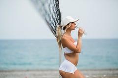 刷新在锻炼以后 体育衣物饮用水的美丽的年轻白肤金发的妇女 库存图片