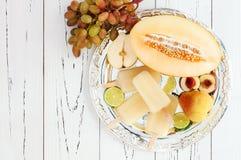 刷新的冰流行在银色盘子 梨,桃子,葡萄,石灰,甘露白色桑格里酒paletas -冰棍儿 顶视图 免版税库存图片