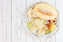 刷新的冰流行在银色盘子 梨,桃子,葡萄,石灰,甘露白色桑格里酒paletas -冰棍儿 顶视图 免版税图库摄影