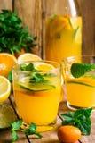 刷新的柑橘柠檬水用新鲜薄荷,玻璃,瓶,在木厨房用桌上的被切的果子 免版税库存图片