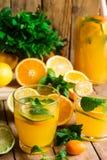 刷新的柑橘柠檬水用薄菏,玻璃,瓶,在木厨房用桌上的被切的果子 库存图片