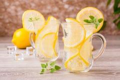 刷新的矿泉水用柠檬、薄菏和冰块在玻璃 库存照片