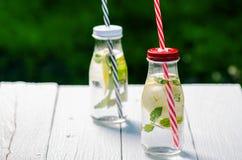 刷新的自创调味的水用柠檬、石灰和盖醇在一张白色桌上在庭院里 新的成人 贝蒂 免版税图库摄影