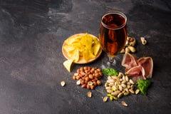 刷新的酒精饮料的顶视图与快餐的 啤酒和咸开胃菜在灰色石背景 复制 库存照片