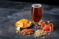刷新的酒精饮料 在玻璃的黑暗的强麦酒 快餐的构成 啤酒和开胃菜在桌背景 免版税库存照片