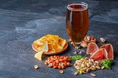 刷新的酒精饮料 在玻璃的黑暗的强麦酒 快餐的构成 啤酒和开胃菜在桌背景 库存照片