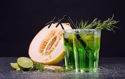 刷新的非酒精饮料 切开瓜和绿色鸡尾酒在黑背景 甜点喝与酒、石灰和龙篙 库存图片