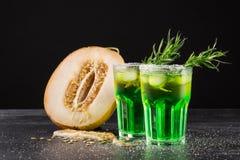 刷新的非酒精饮料 切开瓜和绿色鸡尾酒在黑背景 甜点喝与酒、石灰和龙篙 免版税库存图片