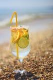 刷新的饮料用在一块玻璃的果子在海滩 库存照片