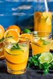 刷新的饮料,柑橘柠檬水桔子撒石灰在瓶和玻璃,在木桌,蓝色背景上的切的果子的新鲜薄荷 库存图片