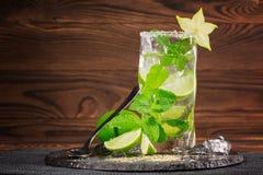 刷新的鸡尾酒用兰姆酒,石灰,薄菏,击碎了冰和阳桃在木背景 酒精mojito玻璃  复制空间 库存图片