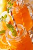 刷新的鸡尾酒用桔子,柠檬,在玻璃瓶子橡皮防水布的冰 库存图片