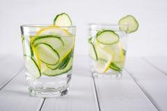 刷新的黄瓜鸡尾酒,柠檬水,在玻璃的戒毒所水 玻璃水瓶柑橘饮料冰橙色夏天水 免版税图库摄影