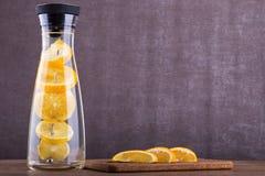 刷新的水用桔子 桔子在水中切a 在一个玻璃瓶子的饮料 在木背景的自创柠檬水 库存照片