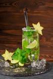 刷新的mojito鸡尾酒的特写镜头在透明高玻璃杯的与在木背景的一把匙子 复制空间 免版税库存照片