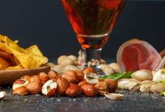 刷新酒精饮料特写镜头  在玻璃的黑暗的强麦酒 快餐的构成 啤酒和开胃菜在桌上 免版税库存照片